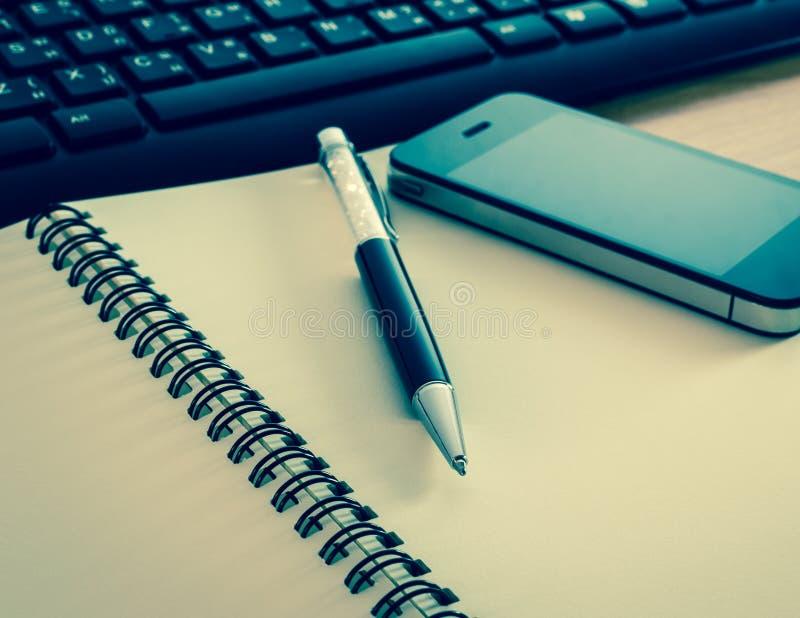 Ручка и сотовый телефон на тетради с клавиатурой стоковые фотографии rf