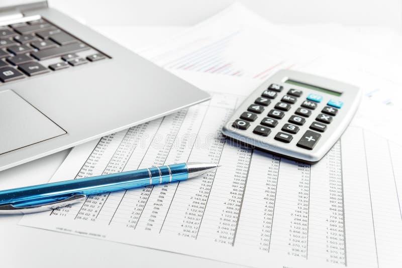 Ручка, калькулятор и компьтер-книжка лежа на финансовом отчете с онемелым стоковое изображение