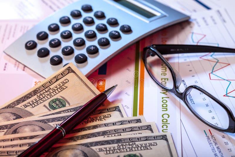 Ручка, калькулятор, Eyeglasses и банкноты дальше стоковые изображения rf