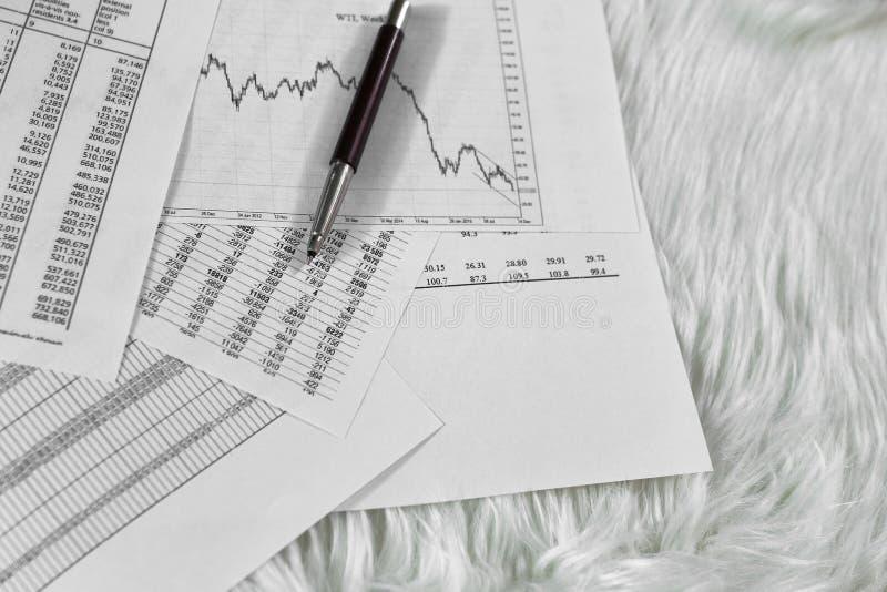 Ручка на бумаге с цитатами и диаграммами цены стоковые фото