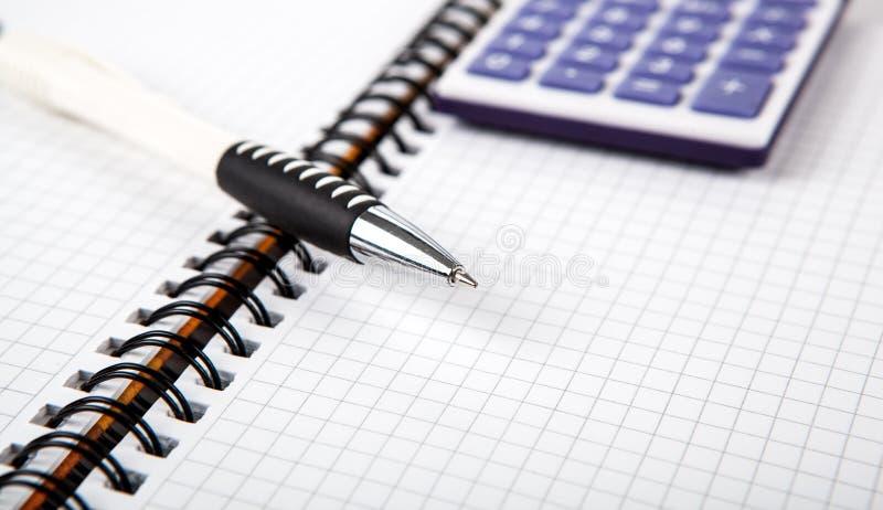 Ручка на тетради в клетку и калькулятор стоковое фото