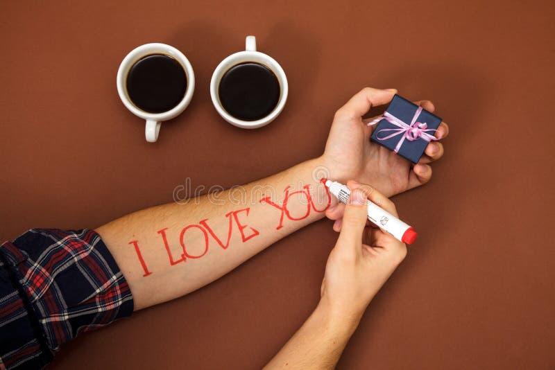 Ручка пишет письму дорогой день ` s валентинки коричневого цвета подарочной коробки кофейной чашки руки красного цвета я тебя люб стоковые фото