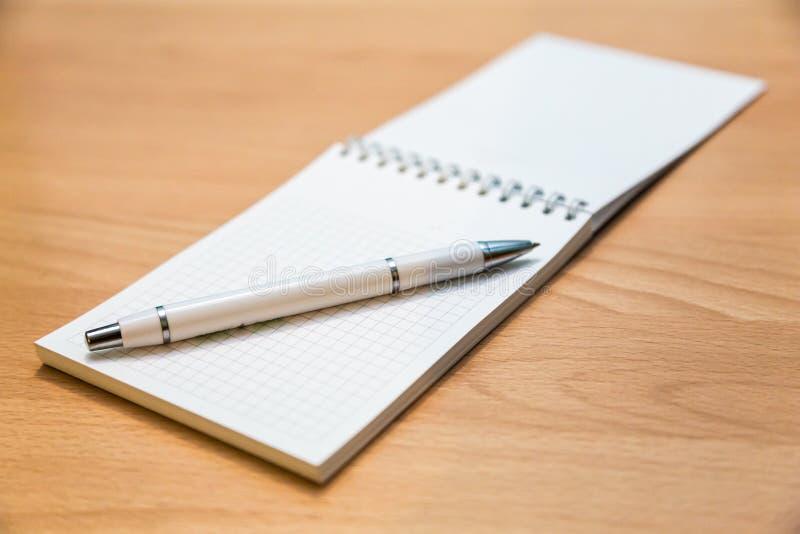 Ручка тетради и шариковой авторучки лежа на деревянном столе стоковая фотография