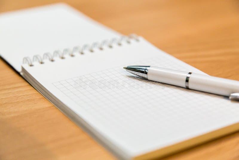 Ручка тетради и шариковой авторучки лежа на деревянном столе стоковое изображение rf