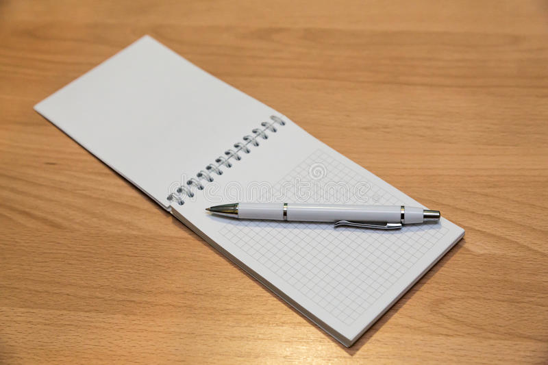 Ручка тетради и шариковой авторучки лежа на деревянном столе стоковое изображение