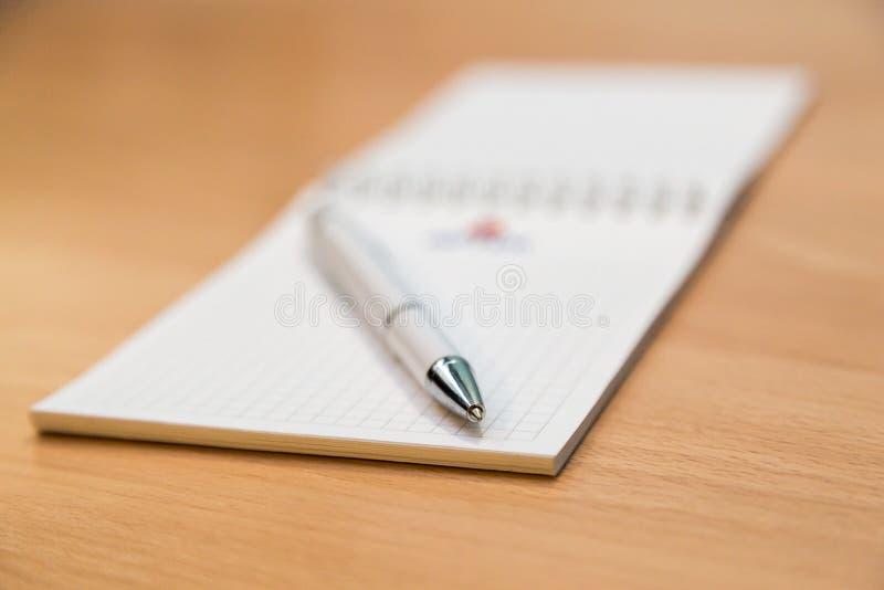 Ручка тетради и шариковой авторучки лежа на деревянном столе стоковые изображения