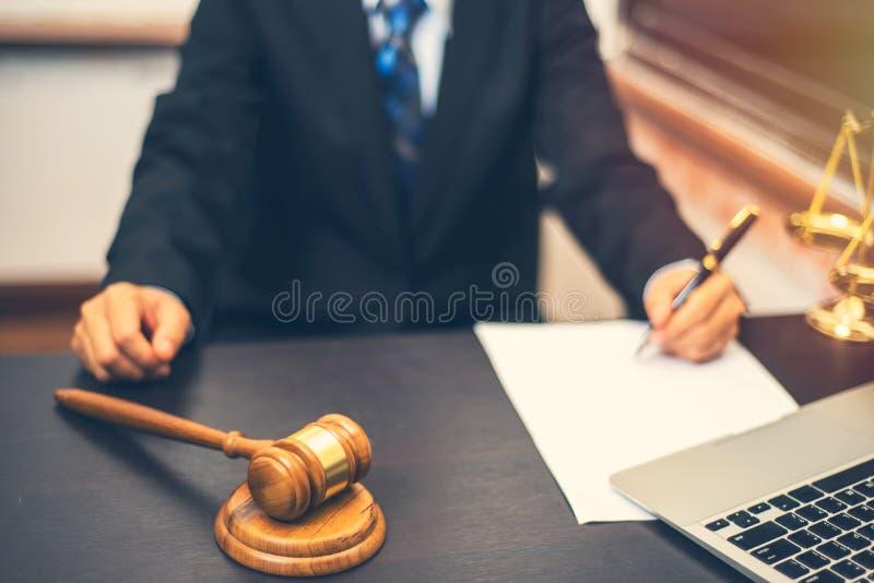 Ручка удерживания юриста с сочинительством на белой бумаге и деревянном молотке стоковые фото