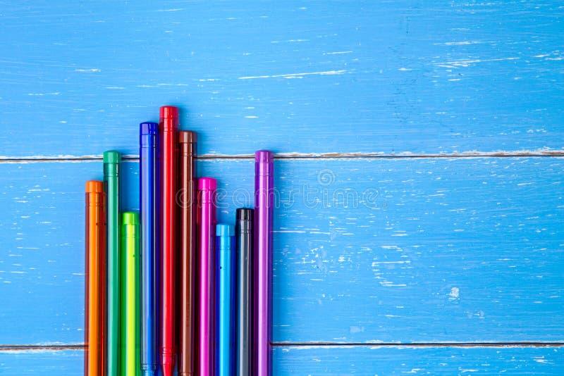 Ручка цвета на голубой деревянной предпосылке стоковые фотографии rf