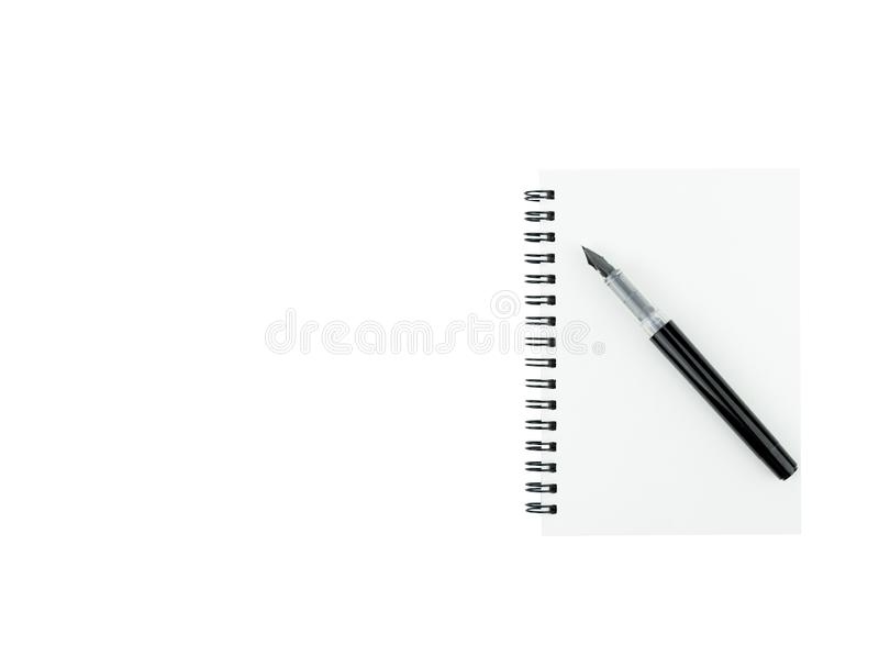 Ручка чернил на блокноте с космосом экземпляра на изолированной белой предпосылке стоковые фотографии rf