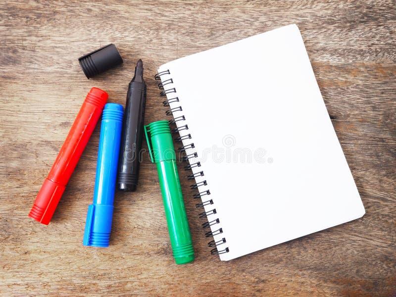 Ручки и тетрадь отметки на деревянной предпосылке Взгляд сверху стоковое фото rf