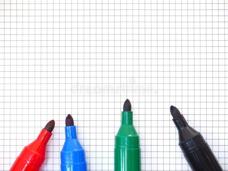 Ручки отметки на предпосылке миллиметровки Взгляд сверху стоковое изображение rf