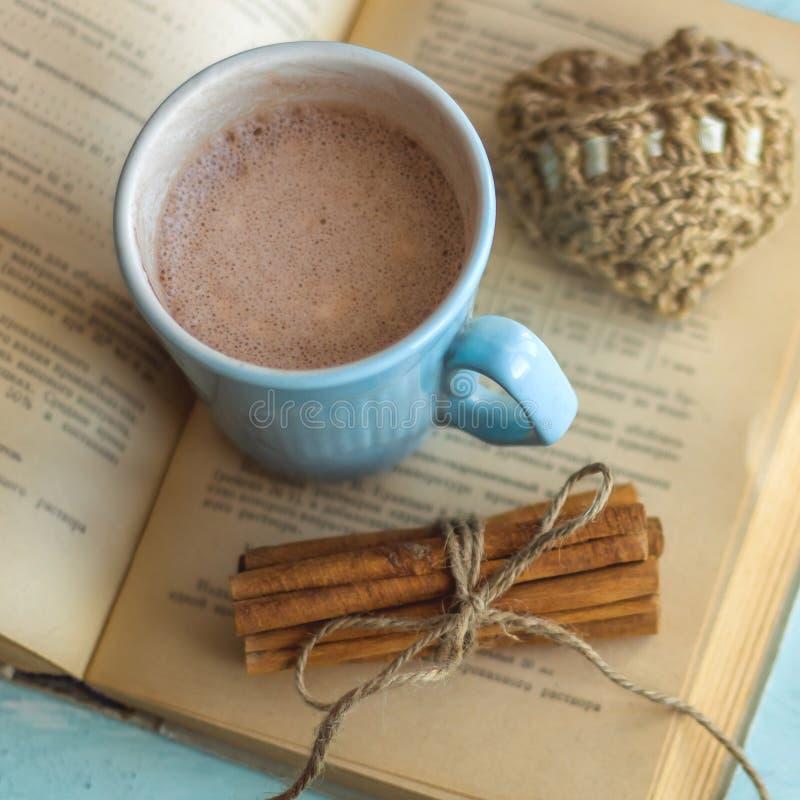 ручки циннамона старой книги чашки какао и связанное сердце стоковое фото
