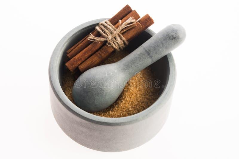 Ручки циннамона с чисто желтым сахарным песком тросточки в миномете стоковое изображение