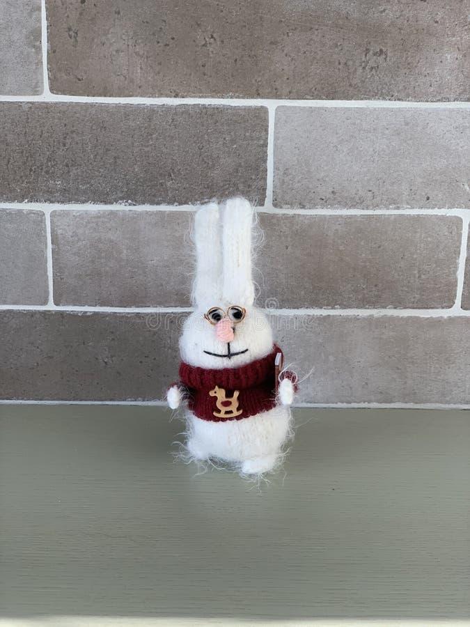 Ручной работы милая умная связанная игрушка или зайцы кролика в красном свитере с лошадью и книгой на положении предпосылки кирпи стоковое фото