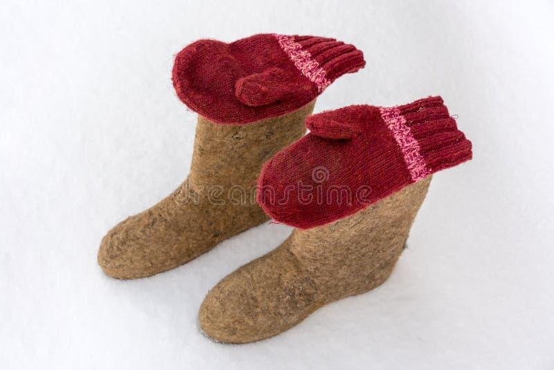Ручной работы valenki и mittens на белом снеге Традиционные русские одежды и ботинки в зиме стоковое изображение rf