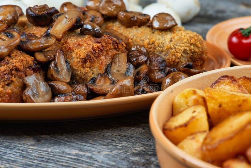 Рулада свинины с зажаренными в духовке грибами и картошками стоковое изображение