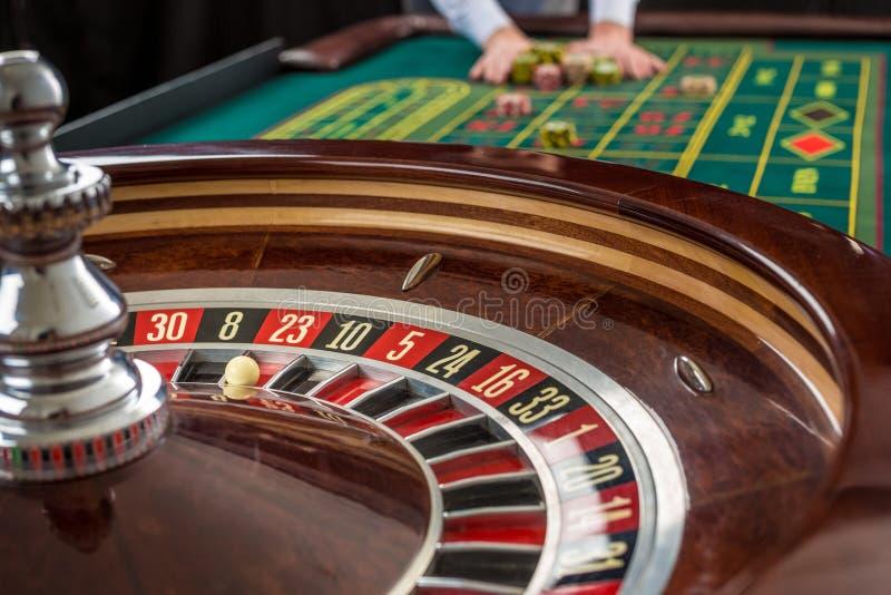 Рулетка и кучи играть в азартные игры откалывают на зеленой таблице стоковая фотография