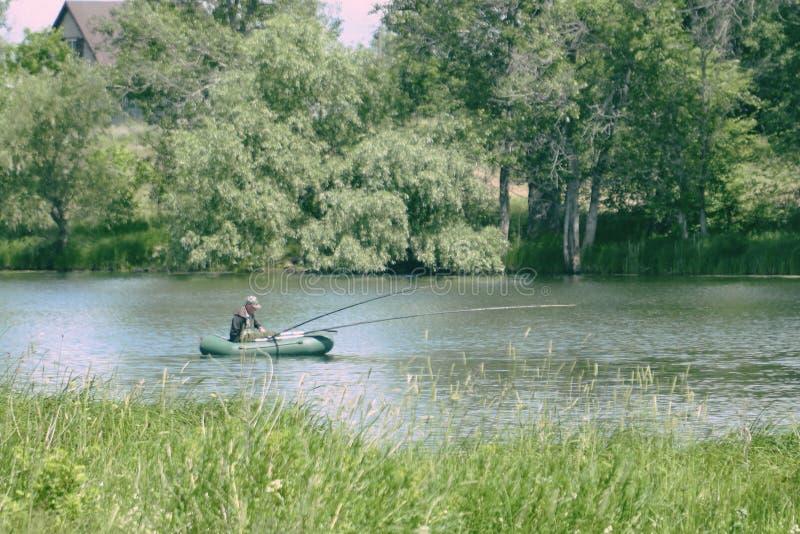 Рыбак в лодке рыбачит на озере стоковое фото