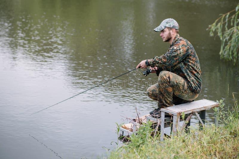Рыбак на летнем фоне Рыбак в руке, держащий спиннинг Рыбная ловля, вращающаяся рельеф, рыба, реки Брег - стоковые изображения rf