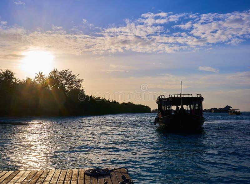 Рыбацкая лодка возвращающ к доку с заходом солнца на своей задней части в курорте hithi bodu кокосов в Мальдивах стоковая фотография rf