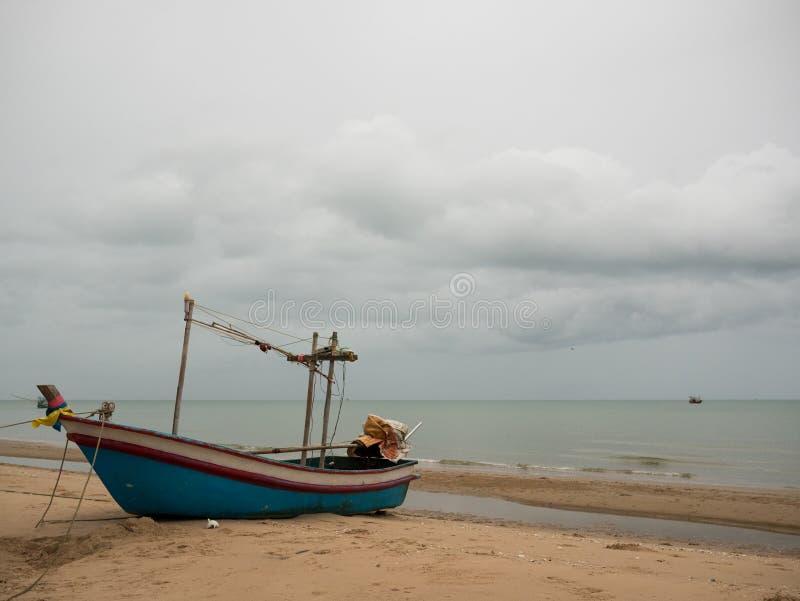 Рыбацкая лодка кальмара на пляже в пасмурном дне утра, с предпосылкой моря стоковые изображения