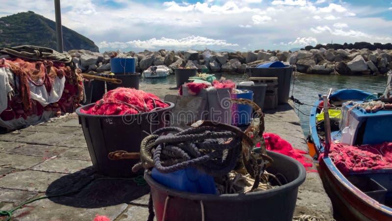 Рыбацкая лодка припарковала около пристани, плавных сеток лежа в корзинах, мелком бизнесе стоковое изображение rf