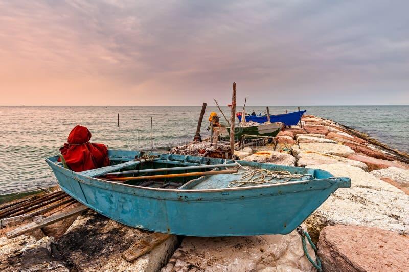 Рыбацкая лодка причаленная на скале на заходе солнца стоковая фотография rf