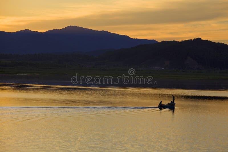 Рыбацкая лодка на озере захода солнца стоковые фотографии rf