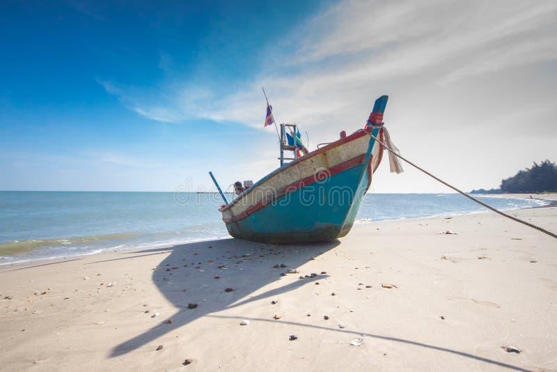 Рыбацкая лодка на пляже с предпосылкой голубого неба в Таиланде стоковое изображение rf