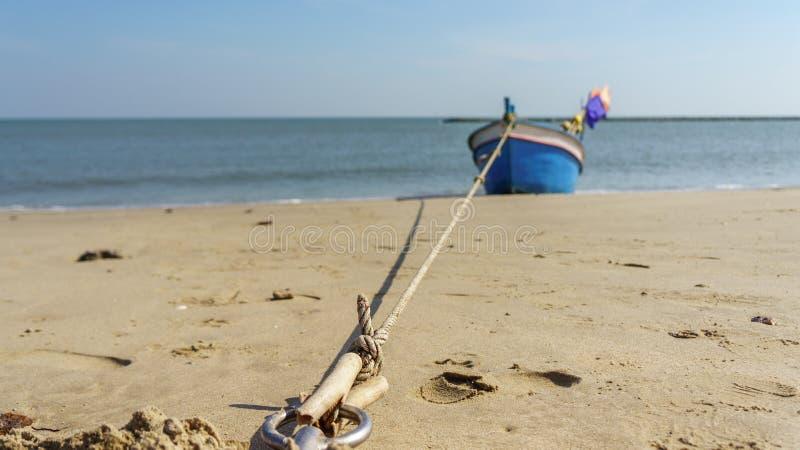 Рыбацкая лодка на пляже с предпосылкой голубого неба в Таиланде стоковые фотографии rf