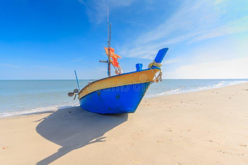 Рыбацкая лодка на пляже с предпосылкой голубого неба в Таиланде стоковое фото