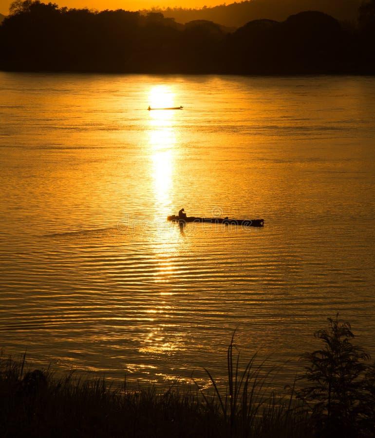 Рыбацкая лодка реки захода солнца стоковое изображение