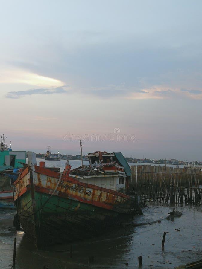 Рыбацкие лодки в плохом состоянии, припаркованном рекой стоковая фотография rf