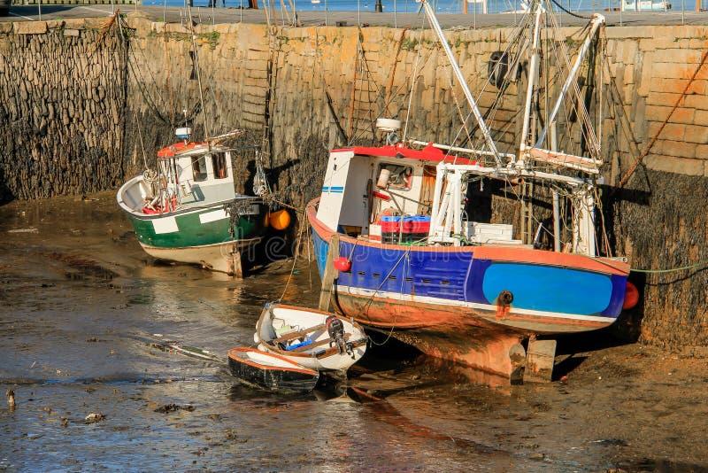 Рыбацкие лодки на грязи во время отлива, защищенный историческими кам стоковая фотография