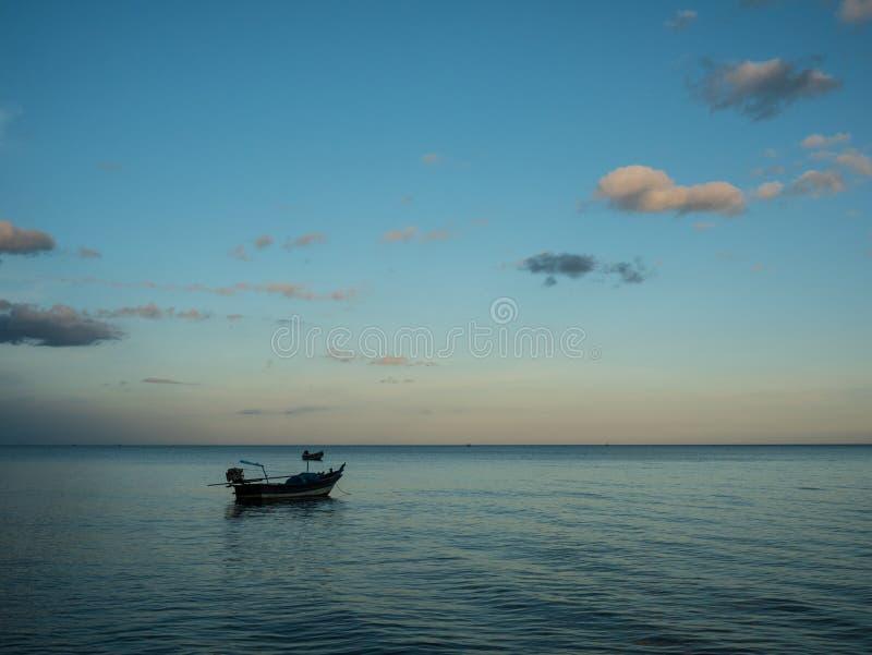 Рыбацкие лодки ставя на якорь на море близко пляжем в заходе солнца стоковое фото rf