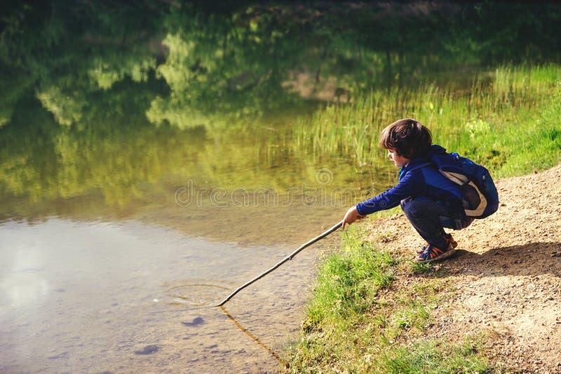Рыбная ловля детской игры около озера стоковое фото