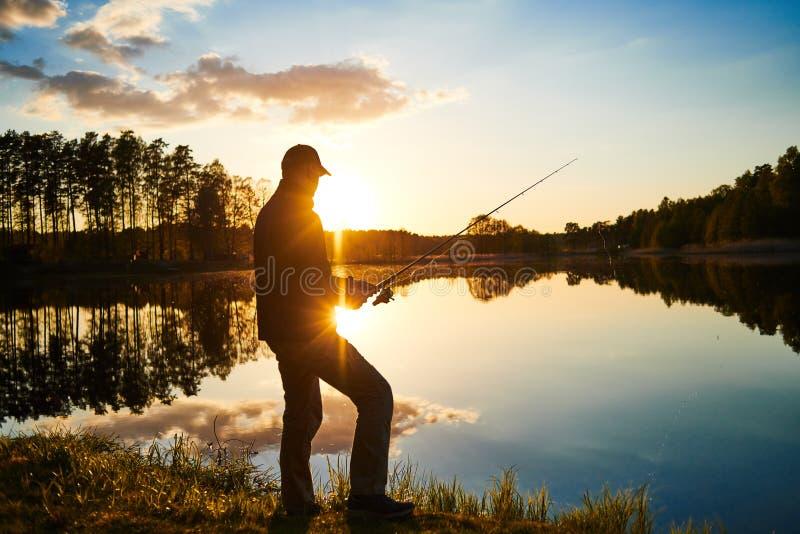 Рыбная ловля захода солнца fisher с закручивая штангой стоковые изображения rf