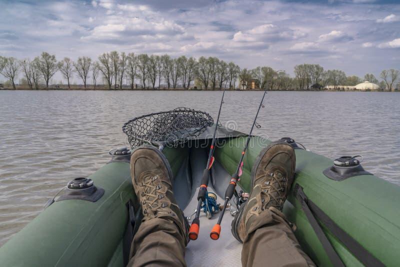 Рыбная ловля каяка на озере Ноги рыболова на раздувной шлюпке с рыболовными снастями стоковая фотография rf