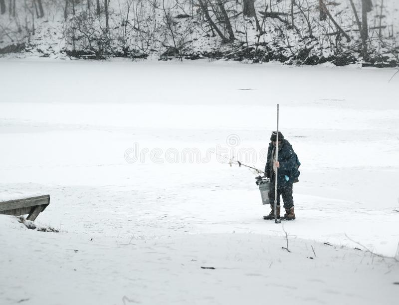 Рыбная ловля льда человека на озере в зиме стоковое изображение rf