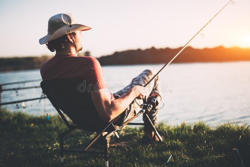 Рыбная ловля молодого человека на пруде и наслаждаться хобби стоковые изображения