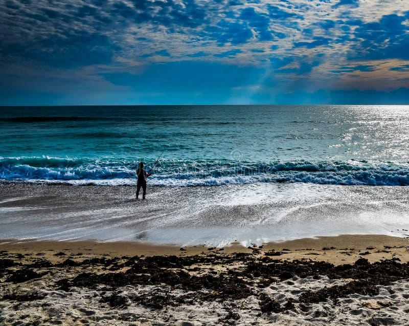Рыбная ловля прибоя в тенях облаков стоковое фото