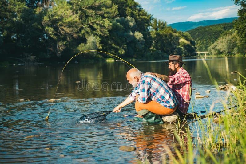 Рыбная ловля стала популярной рекреационной деятельностью Форель рыболова и трофея Рыбная ловля отца и сына Люди поколений стоковые фото