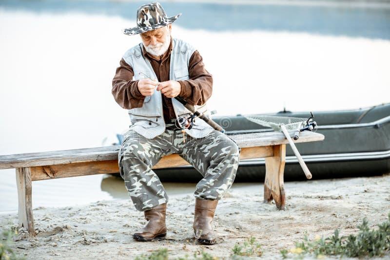 Рыбная ловля старшего человека на озере стоковая фотография