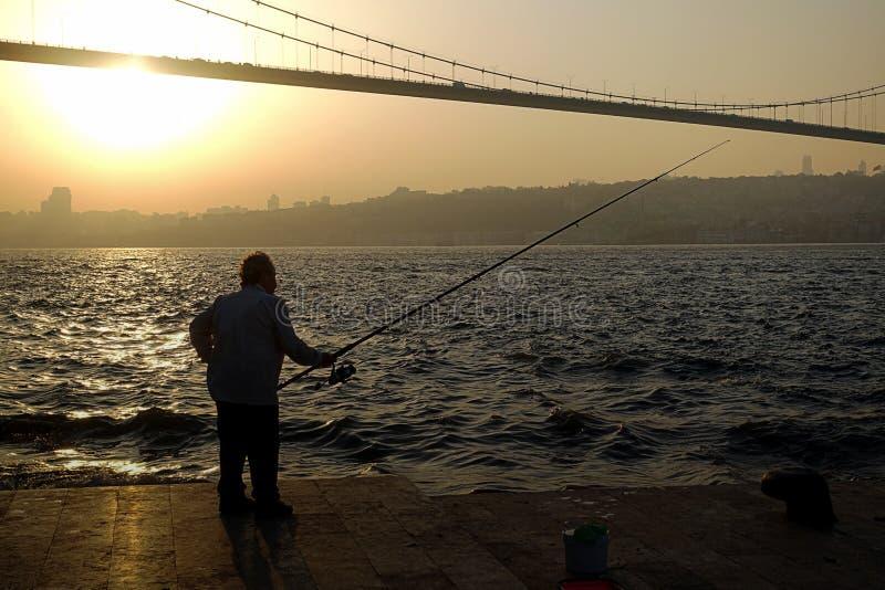 Рыбная ловля человека на побережье перед мостом bosphorus стоковая фотография rf