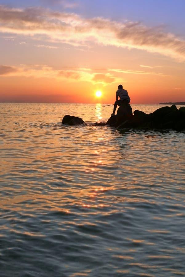 Рыбная ловля молодого человека на взморье во время красивого захода солнца стоковые изображения