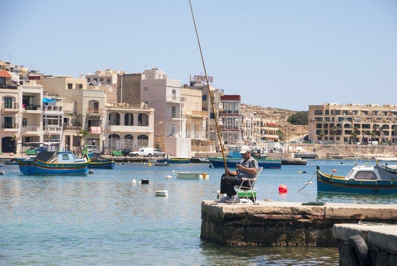 Рыбная ловля рыболова в Marsaskala, Мальте стоковое изображение rf