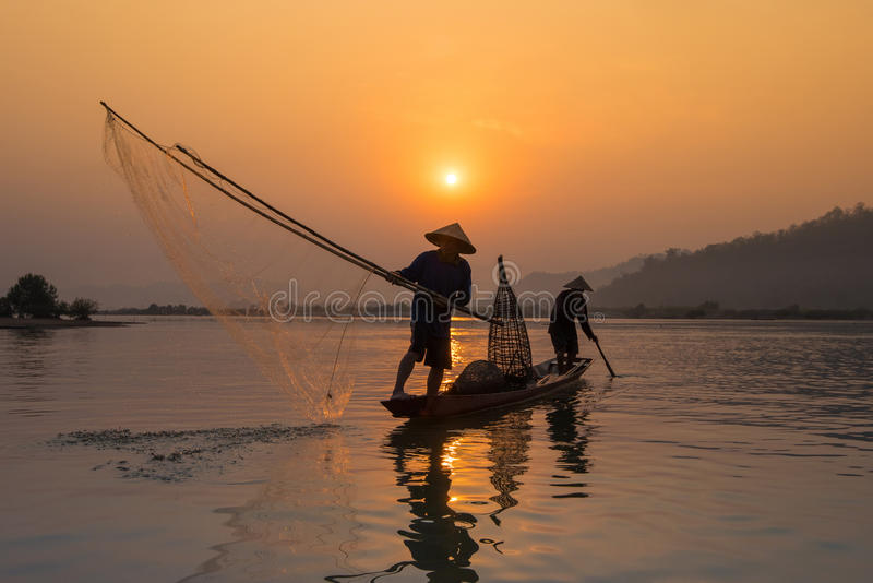 Рыбная ловля рыболова захода солнца стоковое фото