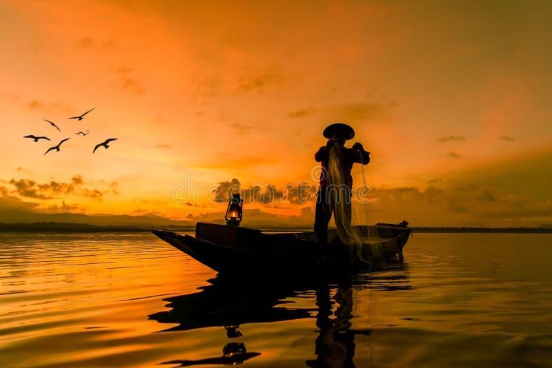 Рыбная ловля рыболова на озере в утре, Таиланде стоковые фото