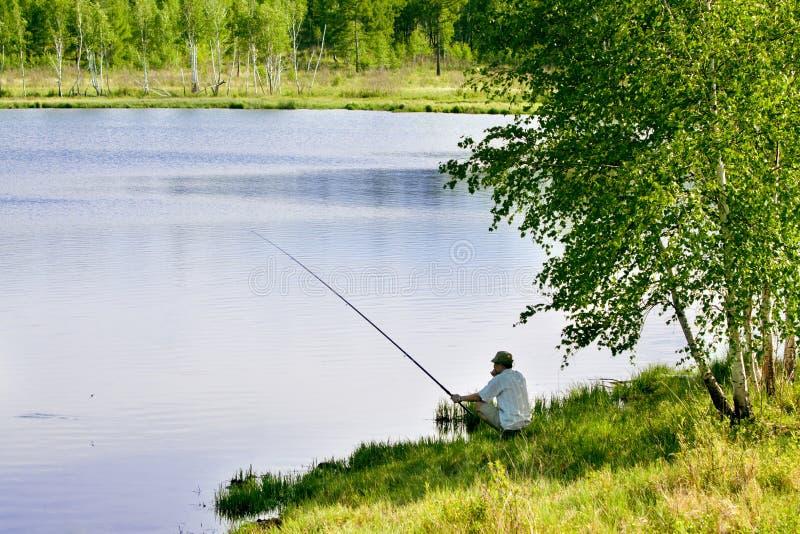 Рыбная ловля рыболова озером стоковые фотографии rf