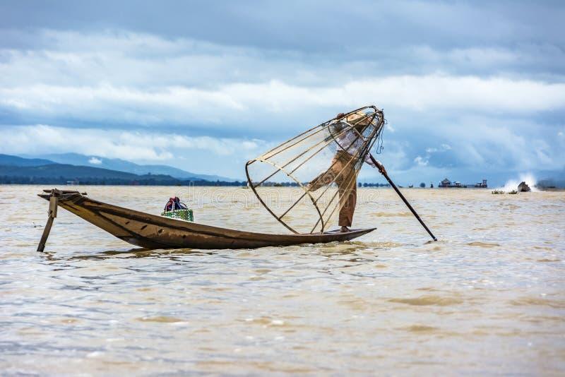Рыбная ловля рыболова Intha в его каное с рыболовной сетью стоковое фото rf